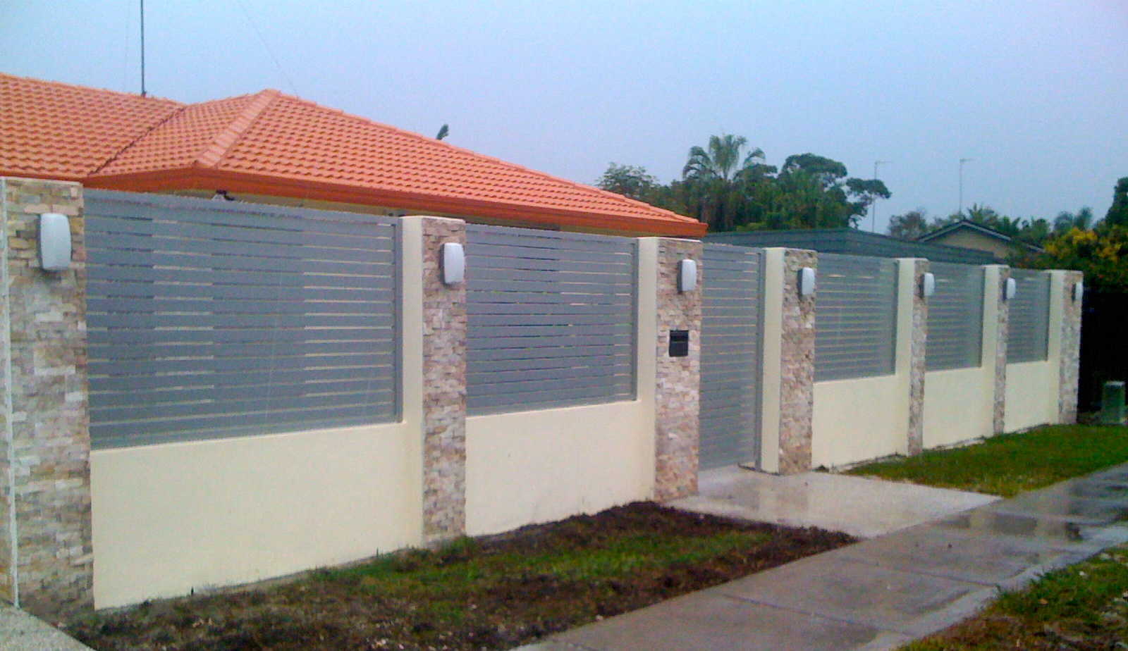 Horizontal slatted panels in front fence